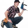 Young manual worker kneeling with power drill — Stock Photo #16838977