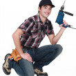 Young manual worker kneeling with power drill - Stock Photo