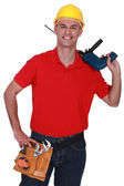 Tradesman holding a power tool — Stockfoto