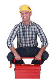 Tradesman struggling to lift his toolbox — Stock Photo