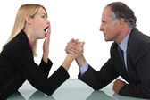 Woman arm wrestling with her boss — Stock Photo