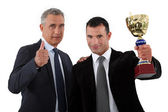 Two businessmen holding trophy — Stock Photo