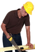 Joiner sawing a plank — Stock Photo