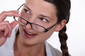Woman putting on her glasses — Foto Stock