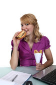 Mujer comiendo una hamburguesa con queso y papas fritas en su escritorio — Foto de Stock