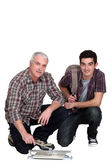 TIler and young teenage apprentice — Stock Photo
