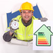 Tradesman holding an energy efficiency rating chart and an alarm clock — Stock Photo