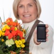 Mature woman showing mobile phone — Stock Photo