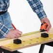 Carpenter measuring a plank - Stock Photo