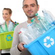 Stock Photo: Mand womrecycling plastic bottles
