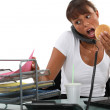 Busy woman eating at her desk — Stock Photo
