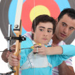 Stock Photo: Boy having archery lesson