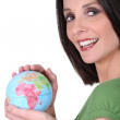 Smiling woman in green holding the world in her hands — Stock Photo