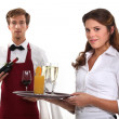 Wine waiter and waitress, studio shot — Stock Photo