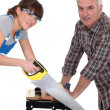 Father and daughter sawing plank of wood — Stock Photo #16849435