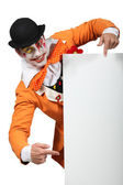 Man dressed up as a joker pointing to a board left blank for your image — Stock Photo