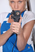 Woman armed with a power drill — Stock Photo