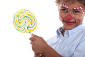 Child made-up holding a lollipop — Stock Photo
