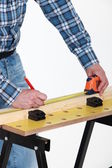 Carpenter measuring a plank — Stock Photo