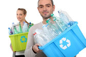 Man and woman recycling plastic bottles — Stock Photo