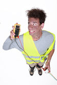 Electrician under shock holding tester — Stock Photo