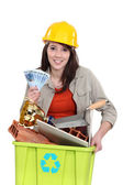 A tradeswoman holding a recycling bin and a wad of cash — Stock Photo