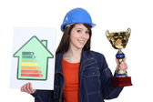 Young woman laborer with energy rating sign and gold cup — Stock Photo