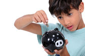 Boy and money box — Stockfoto