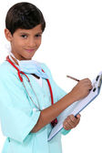 Young boy dressed as a medic with a clipboard — Stock Photo