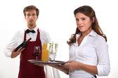 Wine waiter and waitress, studio shot — Stock Photo