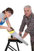 Father and daughter sawing plank of wood — Stock Photo