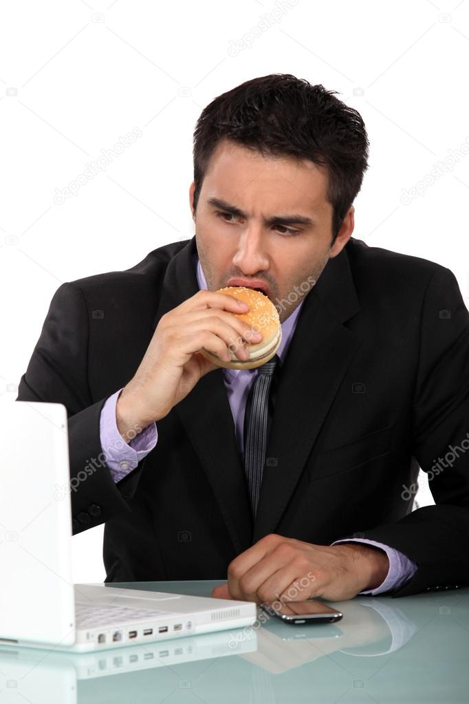 Man eating burger at desk — Stock Photo #16844487