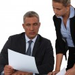 Boss showing paperwork to assistant — Stock Photo