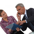 Assistant showing document to boss - Stock Photo