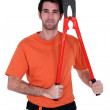 Craftsman holding an enormous pair of pliers — Stock Photo