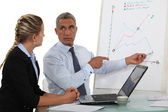 Boss pointing at flip-chart during meeting — Stock Photo