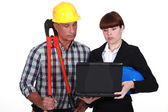 An architect and a foreman looking at a computer. — Stock Photo