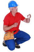 Tradesman holding a plug and a screwdriver — Stock Photo
