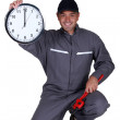 Plumber holding up a clock — Stockfoto