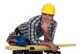 Carpenter casually leaning on work bench — Stock Photo