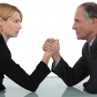 Businessman and woman arm wrestling — Stock Photo