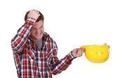 Man with helmet in hand pulling their hair — Stock Photo
