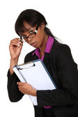 Portrait of intimidating black businesswoman with glasses lowered holding clipboard — Stock Photo