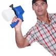 Man holding paint sprayer - Stock Photo