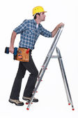 Carpenter with drill climbing step-ladder — Stock Photo