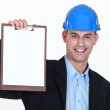 Businessman wearing helmet and holding a notepad — Stock Photo