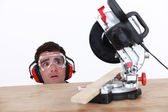 A carpenter afraid of his circular saw. — Stock Photo
