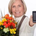 Elderly florist holding flowers and mobile telephone — Stock Photo