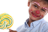 Boy made-up in clown with lollipop — Stock Photo