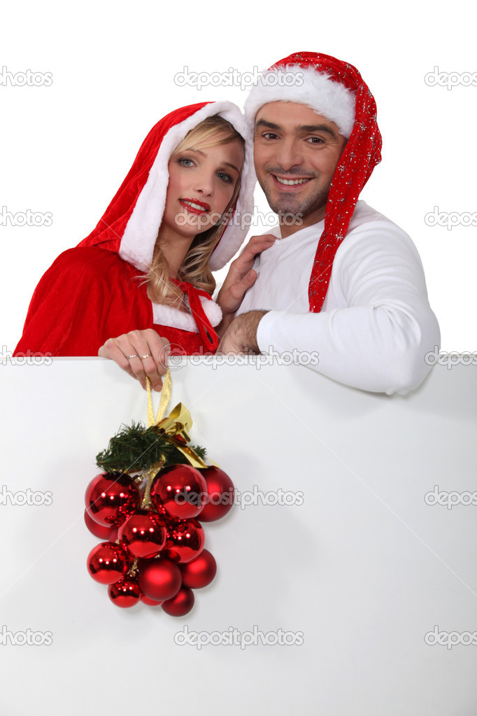 Couple in Santa costumes with a board left blank for your message — Stock Photo #17070105